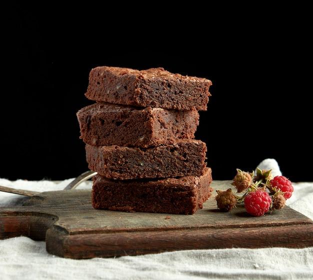 Stapel gebackene quadratische stücke des schokoladenschokoladenkuchenkuchens