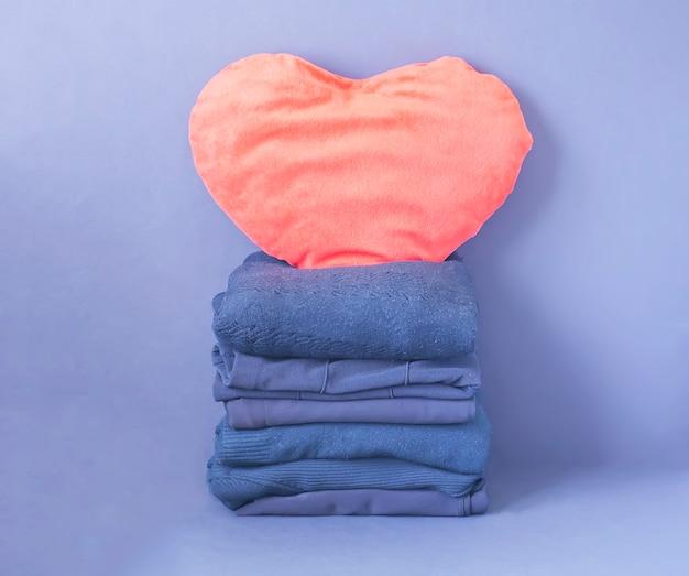 Stapel gefalteter blauer wollkleidung mit rotem plüschherz.