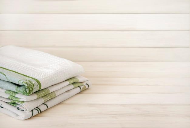 Stapel gefalteter handtücher auf holzuntergrund aus naturmaterialien leinen und baumwolle