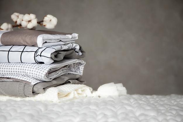 Stapel gefalteter warmer decken mit verschiedenen entwurfsmustern und baumwollzweig auf grauem hintergrund. gestrickte decken. herstellung von natürlichen textilfasern auf pflanzlicher basis. herstellung. bio-produkt