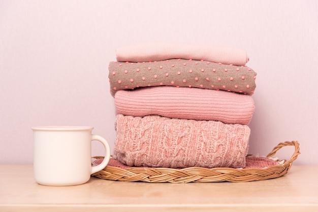 Stapel gefalteter wollstrickpullover in rosa pastellfarben auf tisch mit tasse tee