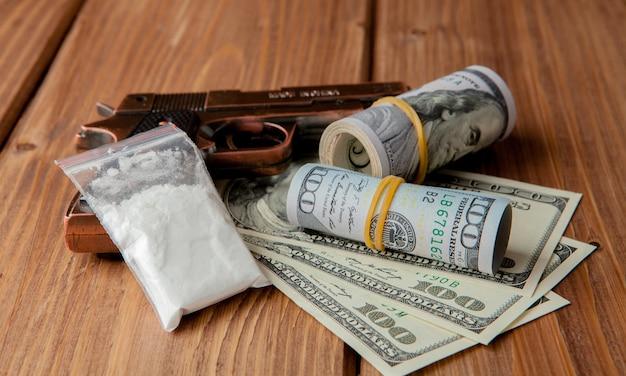 Stapel geld, drogen und eine waffe auf einem holztisch