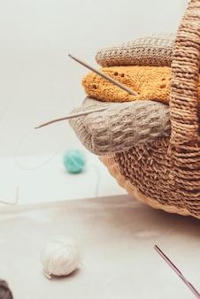 Stapel gemütliche gestrickte strickjacken im weidenkorb