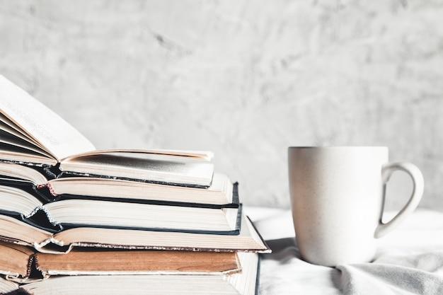 Stapel geöffneter bücher mit einer tasse kaffee im bett