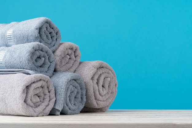 Stapel gerollter handtücher auf einem holztisch