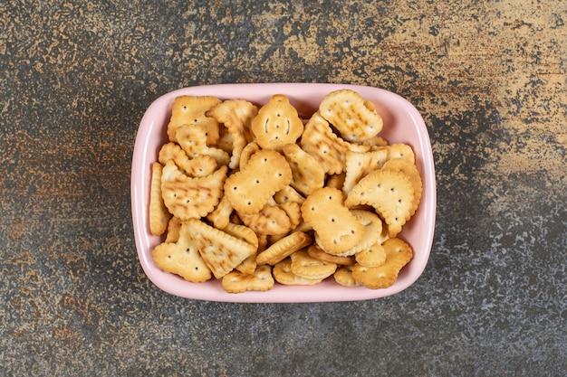 Stapel gesalzener cracker in der rosa schüssel.
