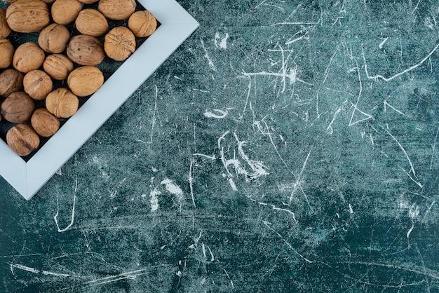 Stapel geschälte walnüsse mit leerem rahmen auf marmortisch.