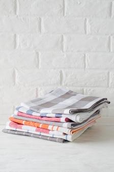 Stapel geschirrtücher oder servietten im innenraum der weißen küche.