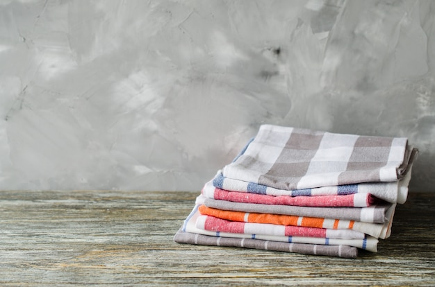 Stapel geschirrtücher oder servietten über dem rustikalen holztisch.