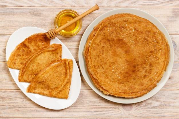 Stapel geschmackvolle pfannkuchen mit honig im glas auf holz
