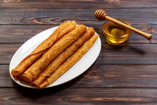 Stapel geschmackvolle pfannkuchen mit honig im glas