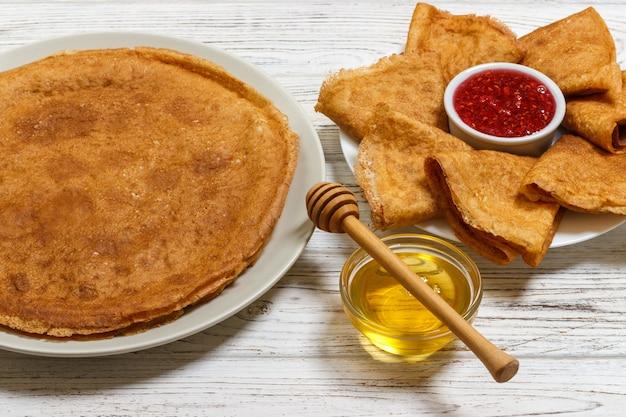 Stapel geschmackvolle pfannkuchen mit honig- und himbeermarmelade im glas
