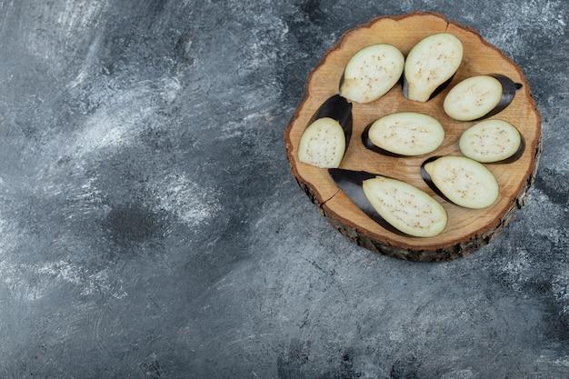 Stapel geschnittener aubergine auf holzbrett. draufsicht.