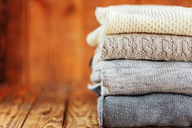 Stapel gestrickte winterkleidung auf hölzernem, strickjacken