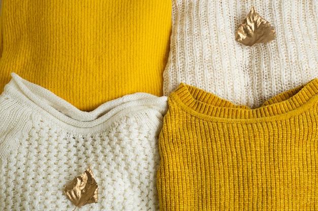 Stapel gestrickter kleidung mit herbstgoldenen blättern