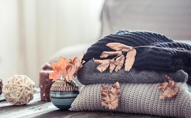 Stapel gestrickter pullover auf einem holztisch