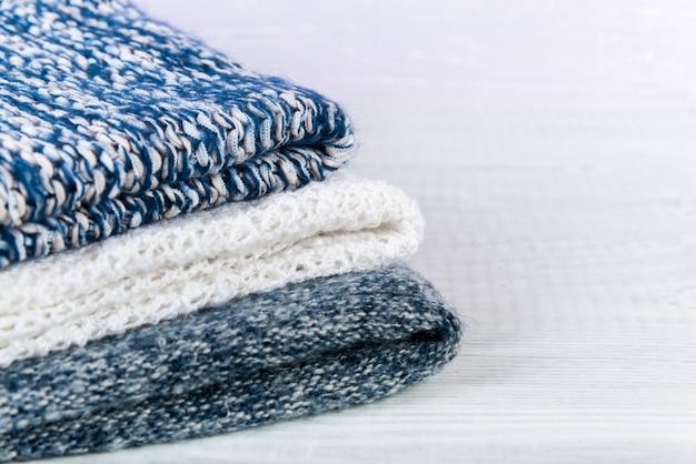 Stapel gestrickter winterkleidung lokalisiert auf weiß