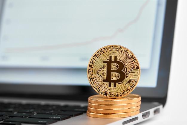 Stapel goldene bitcoins mit einem bitcoin auf seinem rand, der auf laptop mit finanzdiagramm auf seinem schirm steht.