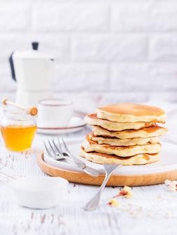 Stapel goldene köstliche pfannkuchen, honig und kaffee