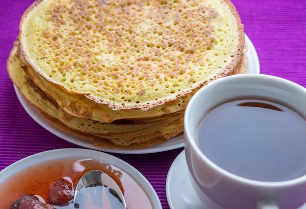 Stapel goldener pfannkuchen mit erdbeermarmelade und tasse tee. nahansicht.