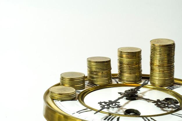 Stapel goldmünzen auf der uhr