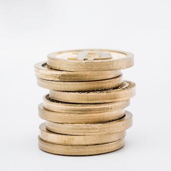 Stapel goldmünzen gegen weißen hintergrund