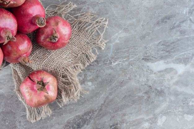 Stapel granatäpfel auf einem stück stoff auf marmor.