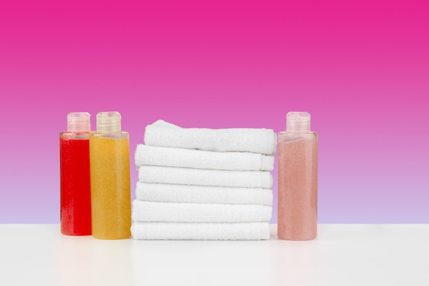 Stapel handtücher flaschen mit shampoo auf weißem tisch