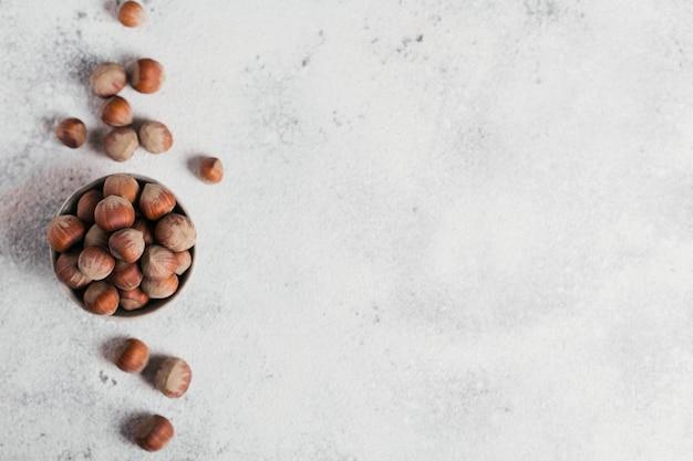 Stapel haselnüsse haselnuss in einer schüssel auf einer weißen oberfläche. frische nüsse in ihren schalen. draufsicht mit freiem platz für text