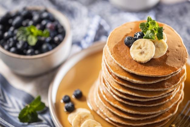 Stapel hausgemachte blaubeerpfannkuchen mit banane, ahornsirup und minze