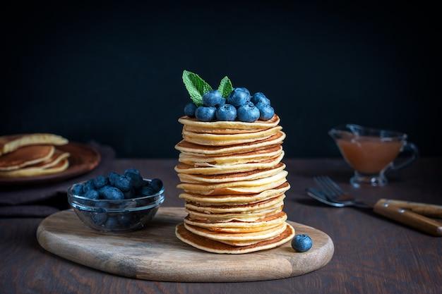 Stapel hausgemachter amerikanischer pfannkuchen, dekoriert mit reifen rohen blaubeeren und minzblättern
