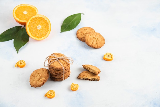 Stapel hausgemachter kekse mit orange und blättern auf weißer oberfläche.