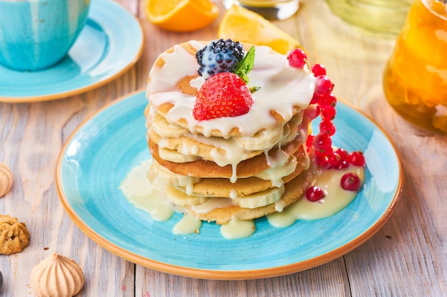 Stapel hausgemachter pfannkuchen mit erdbeere, banane und roter johannisbeere auf einem blauen teller