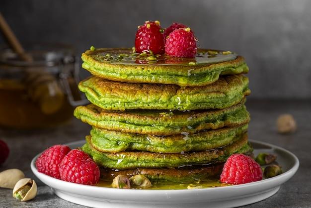 Stapel hausgemachter pfannkuchen mit matcha-tee, frischen himbeeren, pistazien und honig