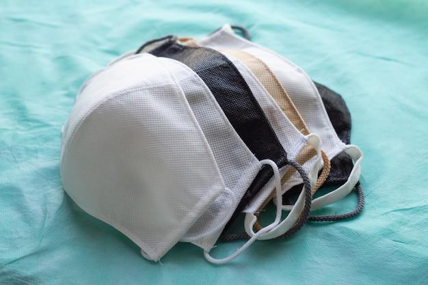 Stapel hausgemachter wiederverwendbarer antiviraler schutzmasken auf grünem tuch