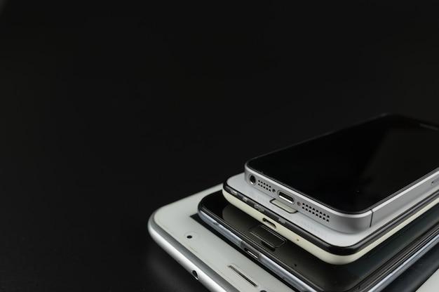 Stapel high-end-smartphones auf schwarzem schreibtisch.
