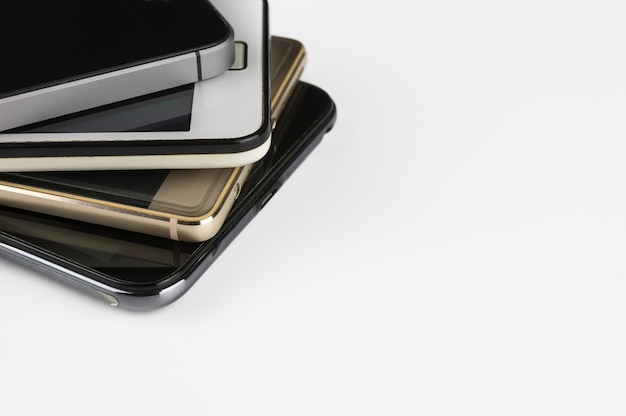 Stapel high-end-smartphones auf weißem schreibtisch.