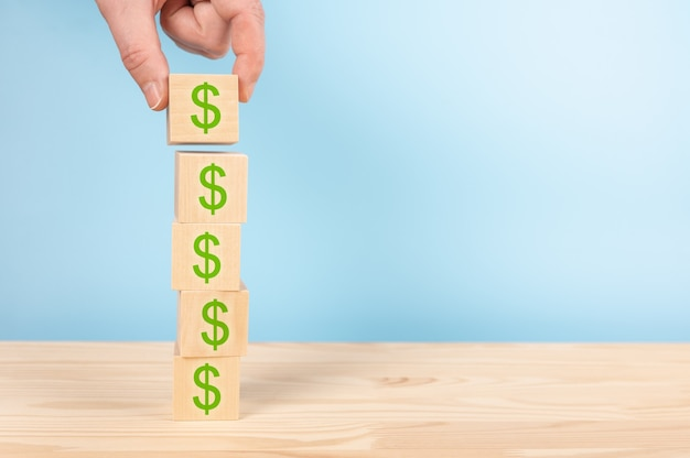 Stapel holzblockwürfel mit dollarzeichen auf tabelle, blauer hintergrund. speicherplatz kopieren. erfolgsprozess des geschäftswachstums