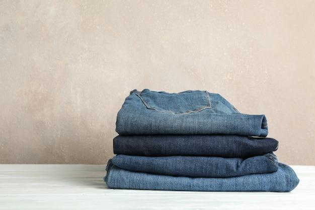 Stapel jeanshosen auf weißem tisch