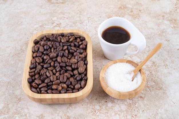 Stapel kaffeebohnen in einer holzplatte neben einer kleinen schüssel zucker und einer tasse kaffee