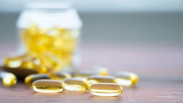 Stapel kapseln omega 3 in glasflasche auf holztisch