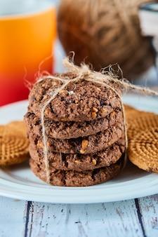 Stapel kekse in teller und korb und eine tasse auf blauem tisch.