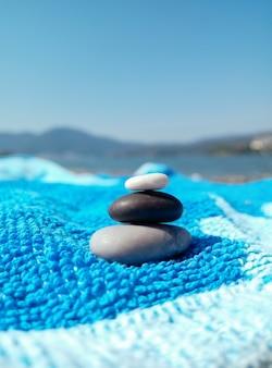 Stapel kieselsteine auf einem blauen strandtuch an einem sonnigen tag viel spaß und entspannung am strand reisen sommerferienkonzept graue schwarze weiße glatte kieselsteine im stapel