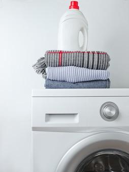 Stapel kleidung, flasche waschgel auf waschmaschine