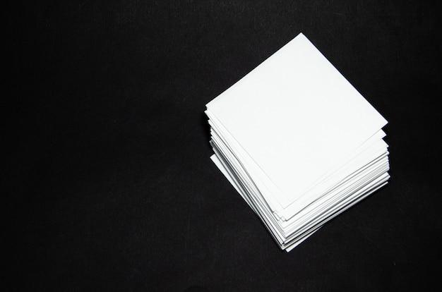 Stapel kleine quadrataufkleber des weißbuches auf schwarzem