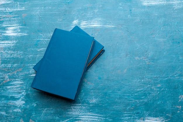 Stapel leere bücher auf der blauen tabelle