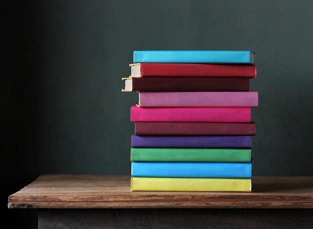 Stapel lehrbücher in der farbigen abdeckung auf dem tisch.