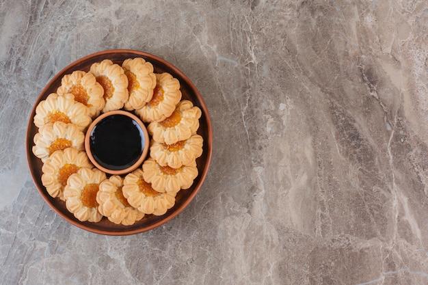 Stapel marmeladenplätzchen mit schokolade auf teller.