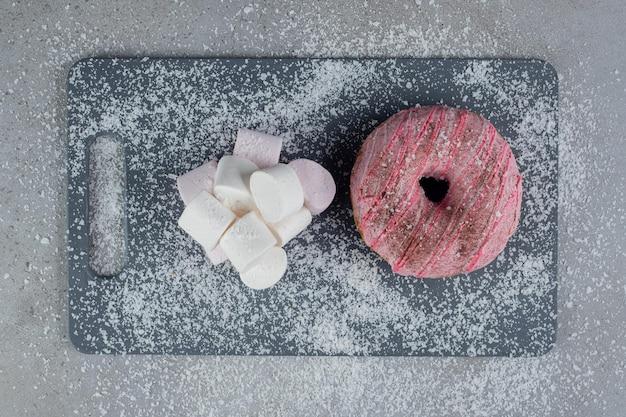 Stapel marshmallows und ein donut auf einem mit kokosnusskraft bedeckten brett auf marmoroberfläche