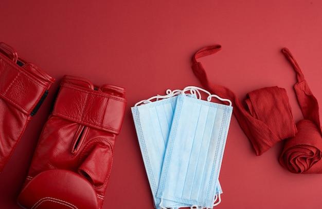 Stapel medizinischer einwegmasken, ein paar boxhandschuhe aus leder und ein roter textilverband